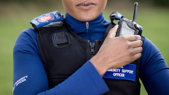 Police Community Support Officer using radio