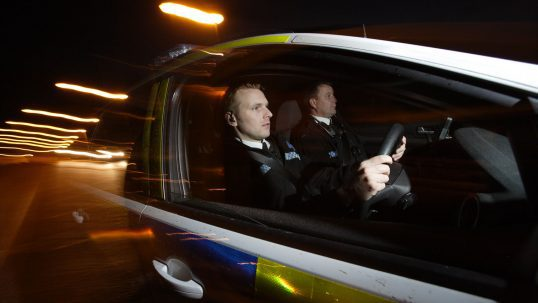 Police officers driving police car at night