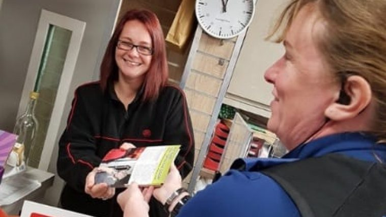 PCSO hands leaflets to Post Office worker