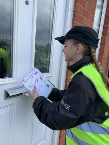 Year 5 Mini Police posting leaflet through letterbox
