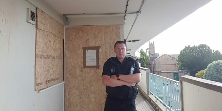 PC outside boarded-up flat