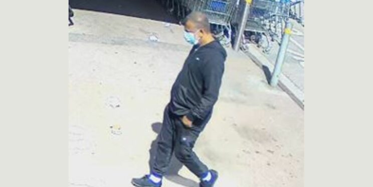 A CCTV image of a man at a supermarket wearing a blue mask