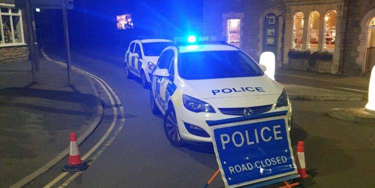 A picture showing two police cars behind a police road closed sign in Cheddar Gorge.