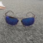 A pair of transparent wayfarer sunglasses with blue lens