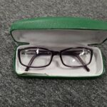 A pair of purple glasses in a green glasses case