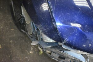 a picture of a damaged front headlight of a blue car