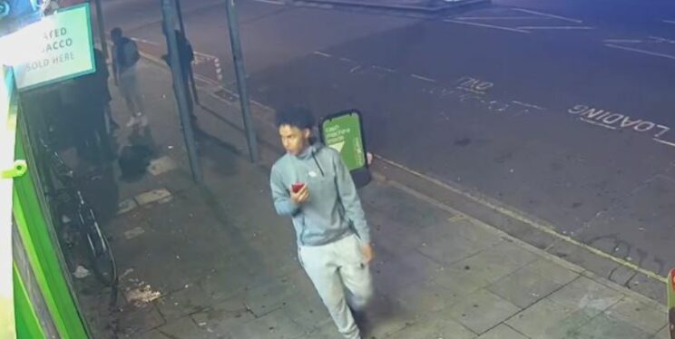 A cctv image of man wearing a grey tracksuit